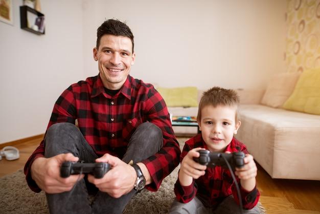 Junger fröhlicher aufgeregter vater und sohn im gleichen roten hemd, die konsolenspiele mit gamepads in einem hellen wohnzimmer spielen.