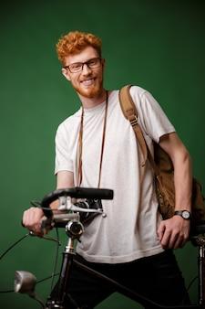 Junger fröhlicher bärtiger hipster mit lesekopf mit rucksack und retro-kamera, stehend auf fahrrad