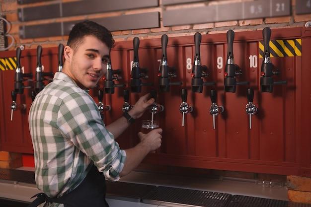 Junger fröhlicher barkeeper, der lächelt, während er bier aus dem wasserhahn einschenkt, raum kopieren