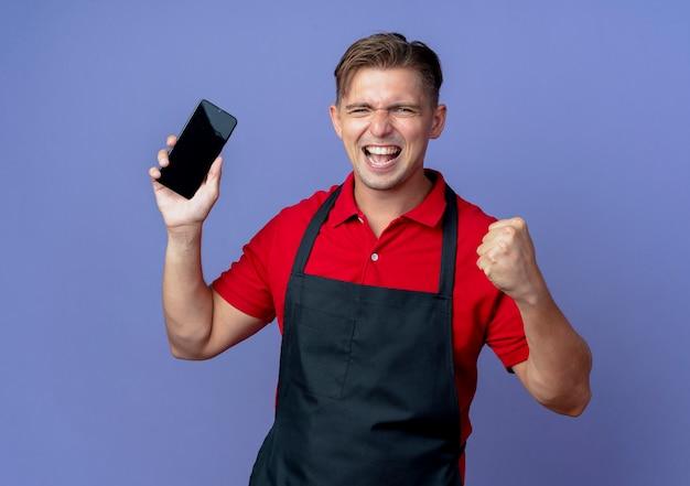 Junger fröhlicher blonder männlicher friseur in uniform hält telefon und hält faust auf violettem raum mit kopierraum isoliert