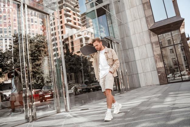 Junger fröhlicher blonder mann, der longboard auf der schulter an der stadtstraße hält. trägt ein beigefarbenes jeans-outfit. sportlicher skateboarder, der draußen über neue extreme tricks nachdenkt.