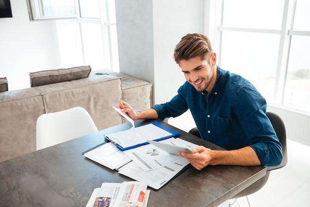 Junger fröhlicher brünetter mann zu hause gekleidet im blauen hemd, das tablette betrachtet und dokumente in der hand hält