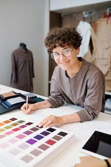 Junger fröhlicher designer von kleidern, die notizen machen und katalog von textilmustern in werkstatt durchsehen