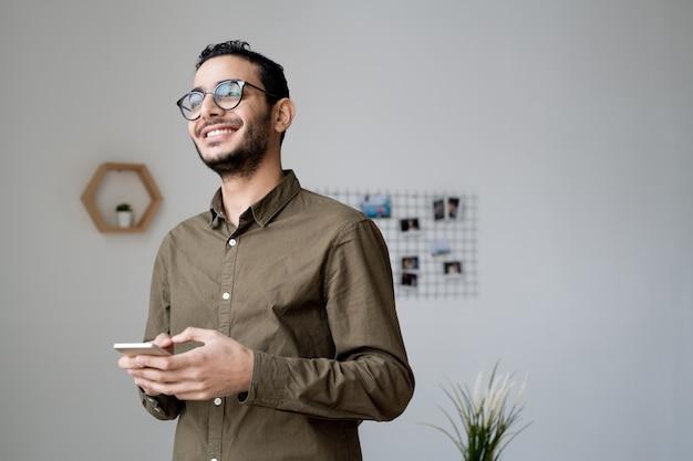 Junger fröhlicher geschäftsmann in den brillen und im freizeithemd, die im smartphone vor bürofenster rollen