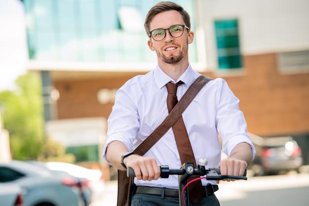 Junger fröhlicher geschäftsmann in der abendgarderobe, der sie beim fahren mit dem fahrrad nach der arbeit in der städtischen umgebung am sommertag betrachtet