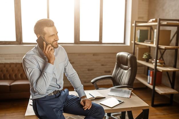 Junger fröhlicher gutaussehender geschäftsmann sitzt auf tisch und telefoniert in seinem eigenen büro. er lächelt. geschäftsgespräch. selbstbewusst und sexy.