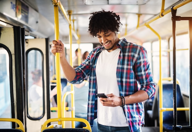 Junger fröhlicher gutaussehender mann genießt die musik während seiner fahrt und hält sich an der bar fest, während er in einem bus steht.
