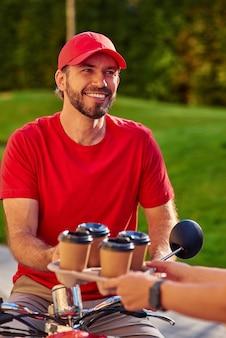 Junger fröhlicher kaukasischer männlicher kurier, der vier kaffeetassen mit dem roller liefert und mit dem kunden spricht. lieferservice-konzept