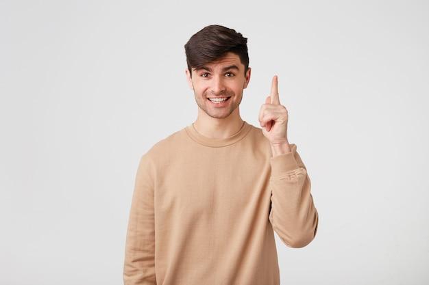 Junger fröhlicher kerl, der zuversichtlich steht und mit dem zeigefinger nach oben zeigt