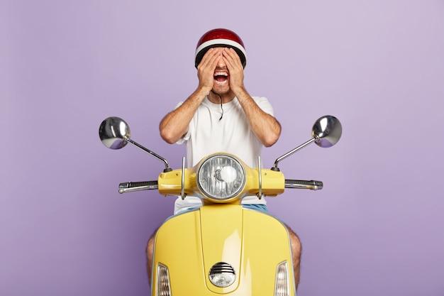 Junger fröhlicher kerl mit helm, der gelben roller fährt