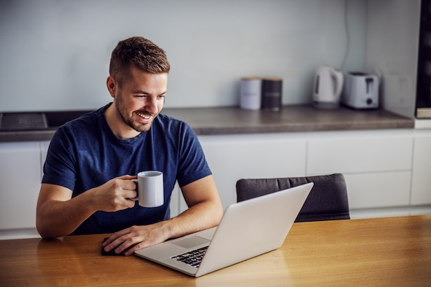 Junger fröhlicher lächelnder mann, der am klingeltisch sitzt, becher mit frischem morgenkaffee hält und laptop betrachtet. er erhält likes für beiträge in sozialen medien.