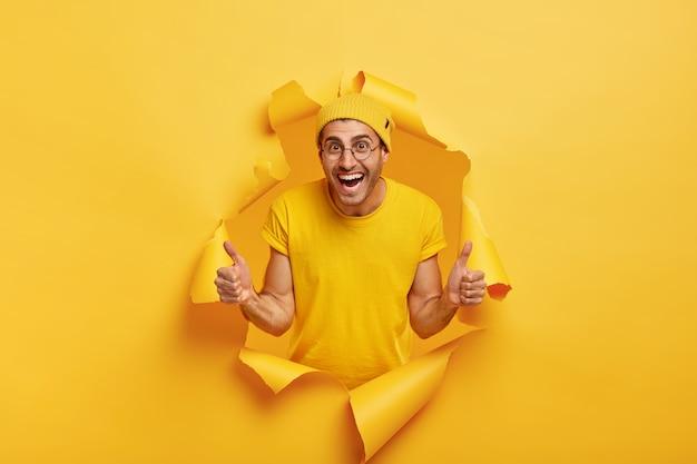 Junger fröhlicher mann, der durch zerrissenes papier aufwirft
