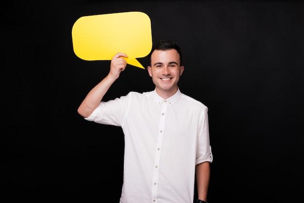 Junger fröhlicher mann, der eine gelbe blasenrede nahe seinem kopf auf schwarzem hintergrund hält.