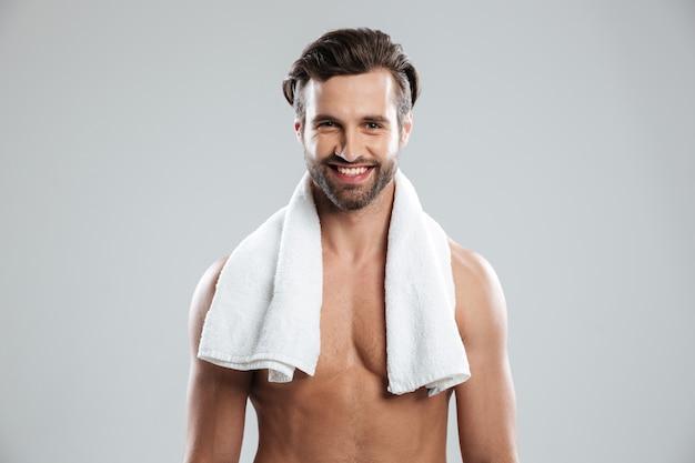 Junger fröhlicher mann, der mit handtuch aufwirft