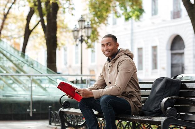 Junger fröhlicher mann, der vorne beim lesen eines buches schaut
