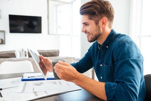 Junger fröhlicher mann gekleidet im blauen hemd, das tablette in der hand hält und kaffee trinkt, während mit dokumenten sitzt