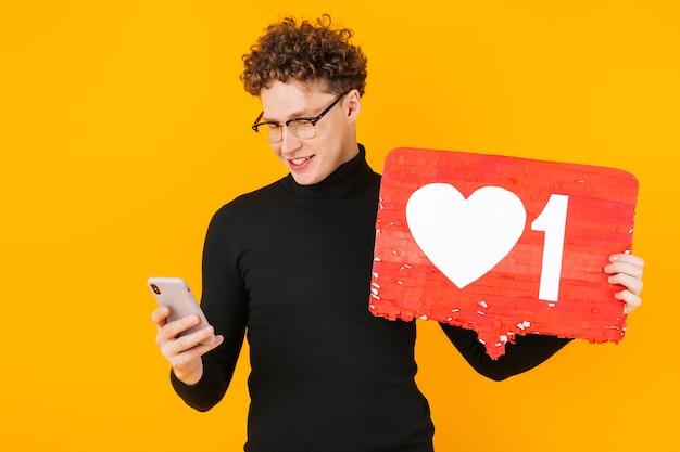 Junger fröhlicher mann mit brille, der ein plakat hält und das handy isoliert auf gelb benutzt