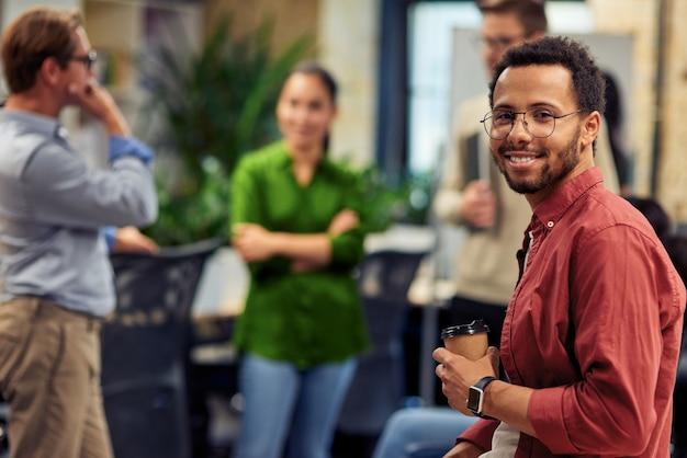 Junger fröhlicher mann mit gemischter rasse, der eine kaffeetasse aus papier hält und während der arbeit in die kamera lächelt