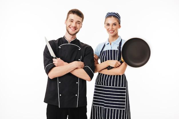 Junger fröhlicher mannkoch in schwarzer uniform mit messer in der hand und hübscher frau kochen in gestreifter schürze und kappe mit pfanne in der hand glücklich