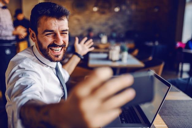 Junger fröhlicher positiver kaukasischer angestellter, der im café sitzt und selfie für soziale medien nimmt.