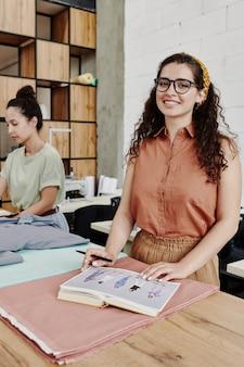 Junger fröhlicher schneider oder modedesigner in kluger freizeitkleidung, der sie beim stehen am tisch in der werkstatt betrachtet und skizzen macht