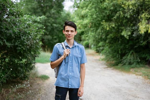 Junger fröhlicher student steht in einem blauen hemd mit einem rucksack auf der straße