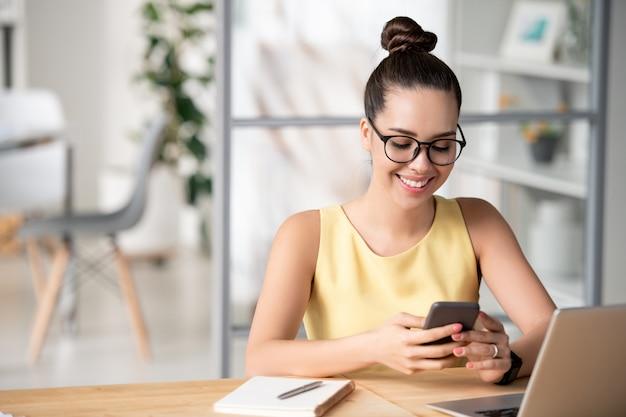 Junger fröhlicher weiblicher manager, der durch nachrichten im smartphone rollt, während er vor laptop sitzt und pause hat