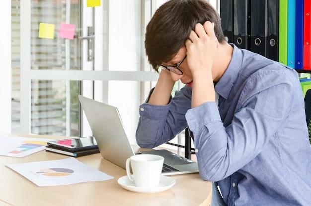 Junger frustrierter asiatischer geschäftsmann auf seiner arbeit und außer kontrolle. stress und kopfschmerzen bei arbeitsunfähigkeit im büro