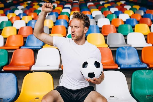 Junger fußballspieler an den tribünen das spiel aufpassend