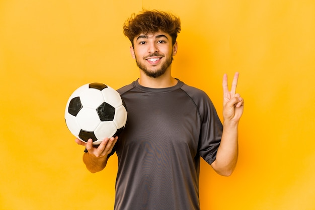 Junger fußballspieler indischer mann, der nummer zwei mit den fingern zeigt.