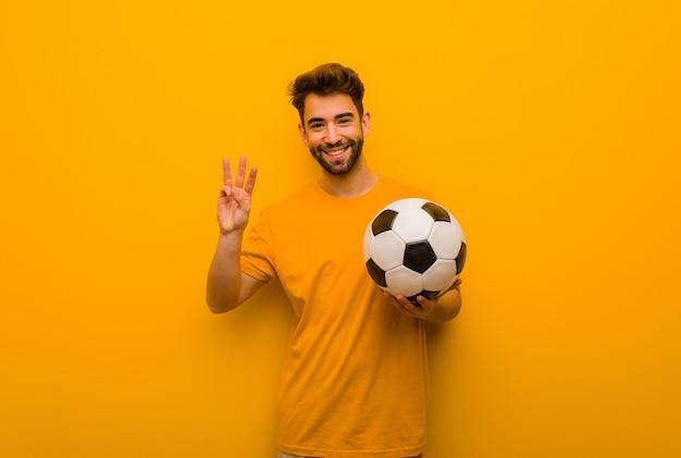Junger fußballspieler mann, der nummer drei zeigt