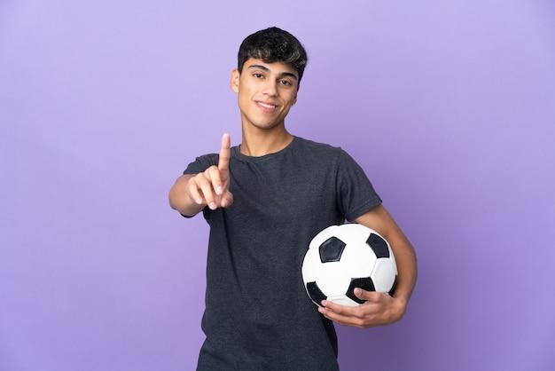 Junger fußballspieler-mann über lokalisiertem lila hintergrund, der einen finger zeigt und anhebt