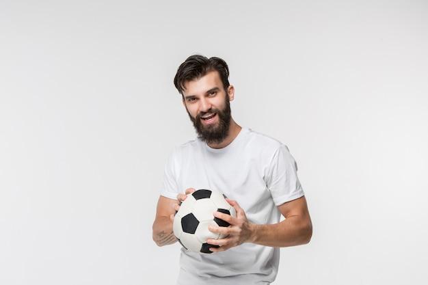 Junger fußballspieler mit ball vor weißer wand