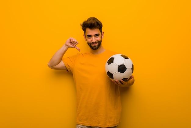 Junger fußballspielermann, der finger, beispiel zeigt, um zu folgen