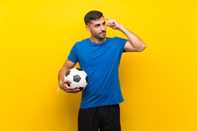Junger fußballspielermann, der zweifel und mit verwirrtem ausdruck hat