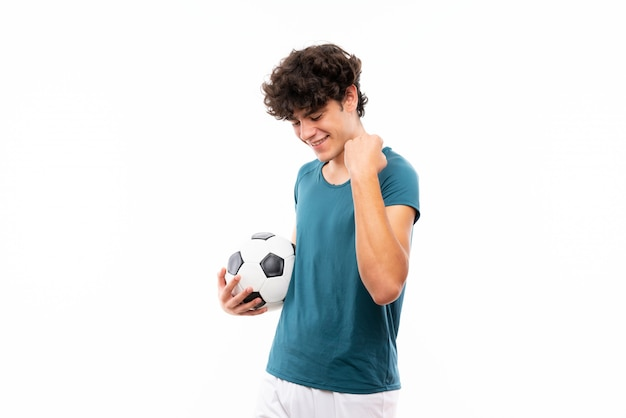 Junger fußballspielermann über der lokalisierten weißen wand, die einen sieg feiert