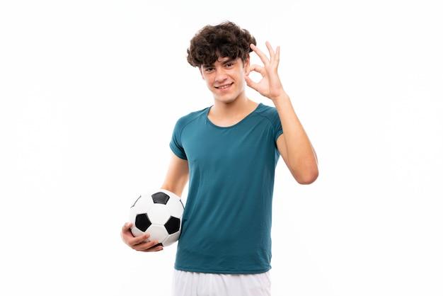 Junger fußballspielermann über der lokalisierten weißen wand, die okayzeichen mit den fingern zeigt