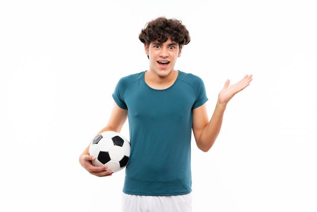 Junger fußballspielermann über lokalisierter weißer wand mit entsetztem gesichtsausdruck