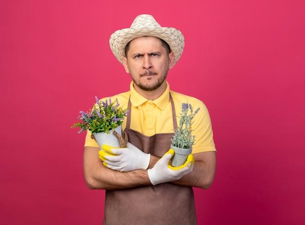 Junger gärtner, der overall und hut in arbeitshandschuhen trägt, die topfpflanzen halten, die vorne mit ernstem gesicht über rosa wand stehen