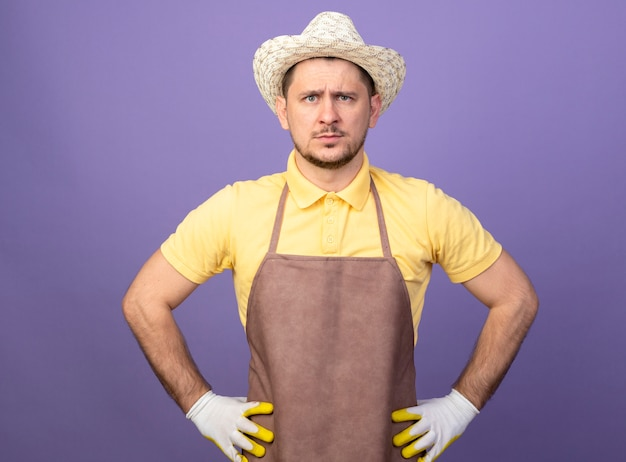 Junger gärtner, der overall und hut in arbeitshandschuhen trägt, die vorne mit ernstem gesicht stehen, das über lila wand steht