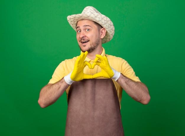 Junger gärtner, der overall und hut in arbeitshandschuhen trägt, macht herzgeste mit den fingern, die nach vorne lächelnd über grüner wand stehend schauen