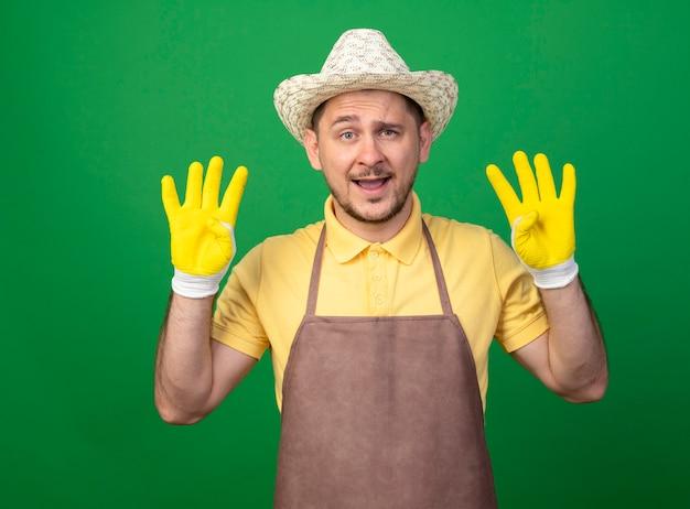 Junger gärtner, der overall und hut in arbeitshandschuhen trägt, zeigt und zeigt mit den fingern nummer acht, die fröhlich über grüner wand stehend lächeln