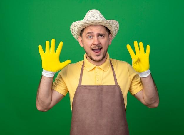Junger gärtner, der overall und hut in arbeitshandschuhen trägt, zeigt und zeigt mit den fingern nummer neun, die fröhlich lächelnd über grüner wand stehen