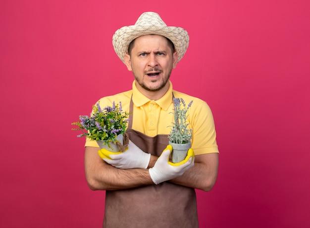 Junger gärtner, der overall und hut in den arbeitshandschuhen trägt, die topfpflanzen halten, die vorne unzufrieden stehen, stehen über rosa wand
