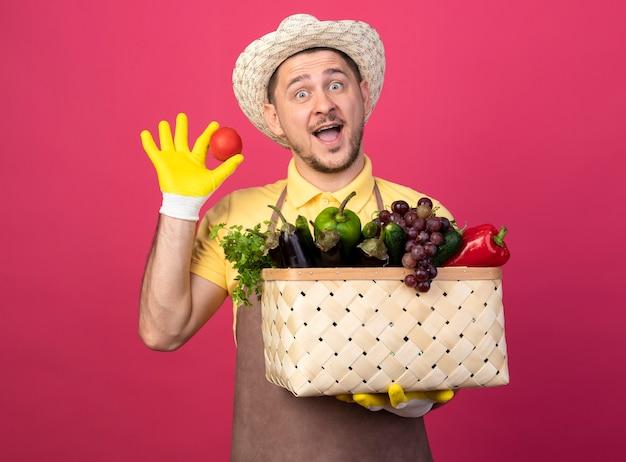 Junger gärtner, der overall und hut in den arbeitshandschuhen trägt, hält kiste voll des gemüses, das frische tomate betrachtet, die vorne lächelnd glücklich und positiv steht über rosa wand