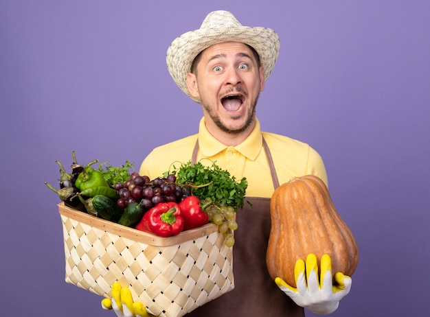 Junger gärtner, der overall und hut in den arbeitshandschuhen trägt, hält kiste voll von gemüse und kürbis, die vorne glücklich und aufgeregt stehen über lila wand stehen