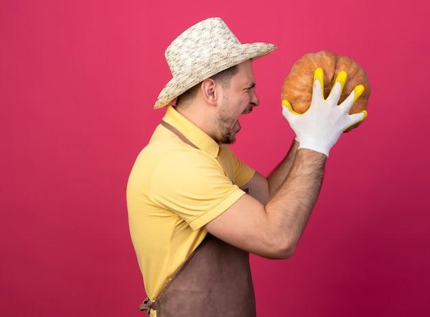 Junger gärtner, der overall und hut in den arbeitshandschuhen trägt, hält kürbis, der seitlich steht und mit aggressivem ausdruck über rosa wand schreit