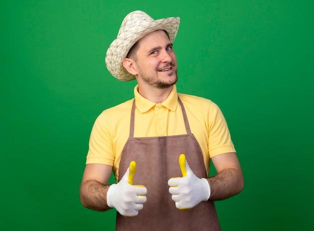 Junger gärtner, der overall und hut in den arbeitshandschuhen trägt, schaut nach vorne lächelnd und zeigt fröhlich daumen hoch stehend über grüner wand
