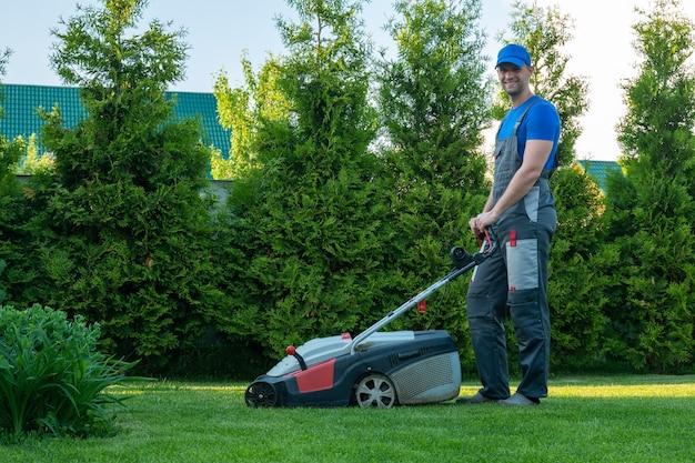 Junger gärtner im overall benutzt einen rasenmäher auf dem grundstück