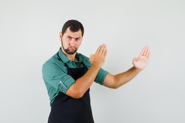 Junger gärtner im t-shirt, schürze, die karate-kotelett zeigt und aggressiv aussieht, vorderansicht.